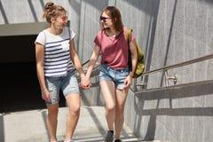 Het openluchtschot van vrouwen heeft homoseksuele verhoudingen, stelt dichtbij ondergronds kruising, bekijkt elkaar met geluk, sl royalty-vrije stock foto