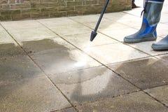 Het openluchtvloer schoonmaken met de straal van het hoge drukwater stock afbeelding