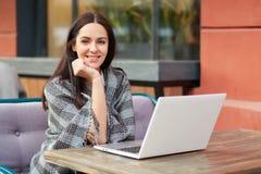 Het opgetogen mooie vrolijke vrouwelijke model freelancer, denkt over idee voor publicatie, gebruikt laptop computer, binnen doet stock afbeeldingen
