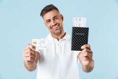 Het opgewekte emotionele volwassen mens stellen geïsoleerd over blauw muur achtergrondholdingspaspoort met kaartjes en creditcard royalty-vrije stock fotografie