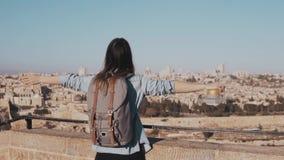 Het opgewekte Europese toeristenmeisje heft gelukkige handen op Israël, Jeruzalem Vrouw met wapens brede open Vrijheid Langzame M stock videobeelden