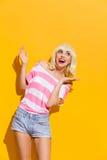Het opgewekte glimlachende blonde spreidde haar handen uit Stock Foto