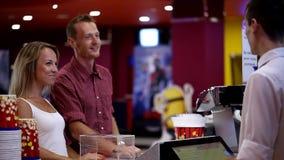 Het opgewekte jonge gelukkige aantrekkelijke paar die van het kerelmeisje popcornorde van mannelijke kassiersarbeider maken bij b stock video