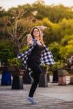 Het opgewekte meisje dansen en het luisteren muziek met hoofdtelefoons slimme telefoon in de straat royalty-vrije stock afbeelding