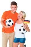 Het opgewekte paar die van de voetbalventilator bij camera toejuichen Royalty-vrije Stock Foto