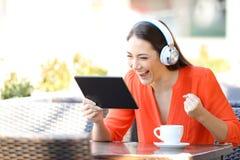Het opgewekte vrouw letten op en het luisteren media op tablet royalty-vrije stock foto