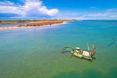 Het opgravende zand van de baggermachineboot voor strand in ondiep water dichtbij stad van Nin stock fotografie
