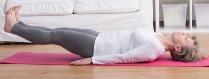 Het opheffen van benen tijdens yoga stock afbeelding
