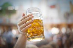 Het opheffen van bierstenen bierkroezen in Oktoberfest stock fotografie