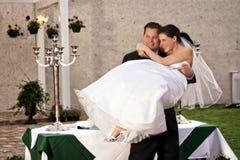 Het opheffen van de bruidegom bruid het lachen Stock Afbeelding