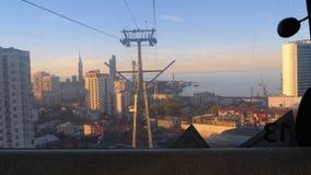 Het opheffen van de kabelwagen in Batumi Weergeven van de cabine op wolkenkrabbers, huizen, en straten stock videobeelden