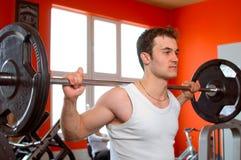 Het opheffen van de mens gewichten bij de gymnastiek Stock Foto's