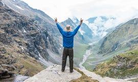 Het opheffen van Handen op de rand van een berg in de Bergketen van Himalayagebergte stock foto's