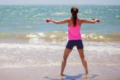 Het opheffen van sommige gewichten bij het strand Stock Foto's