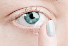 Het opnemen van een contactlens in vrouwelijk oog stock fotografie