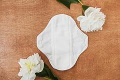 Het opnieuw te gebruiken eco natuurlijke stootkussen voor menstruele dagen met vlakke pioenbloemen, legt r royalty-vrije stock afbeelding