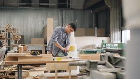 Het oppoetsende hout van de fabrieksarbeider met elektrische machine in ruime workshop stock videobeelden