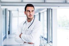 Het optimistische mannelijke arts stellen bij het ziekenhuis binnen stock afbeeldingen