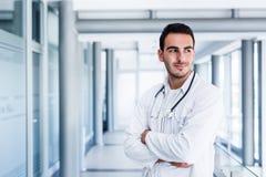 Het optimistische mannelijke arts stellen bij het ziekenhuis binnen stock foto