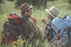 Het optimistische meisje en de kerel eten in openlucht stock afbeeldingen