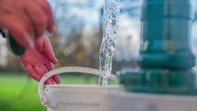 Het opvullen van de emmer vanaf historische waterpomp stock video