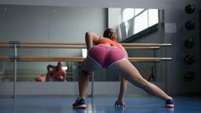 Het opwarmen alvorens op te leiden Jonge vrouw in sportkleding die het uitrekken doen zich terwijl status voor venster bij gymnas stock footage