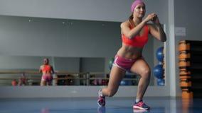 Het opwarmen alvorens op te leiden Jonge vrouw in sportkleding die het uitrekken doen zich terwijl status voor venster bij gymnas stock videobeelden