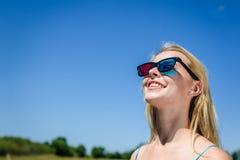Het opwekken van mooie jonge dame het letten op film met 3D glazen, lichtblauwe achtergrond Stock Foto's