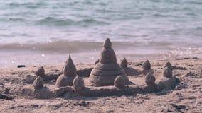 Het opwekken van nat zandkasteel met torens en omheining op strand stock footage