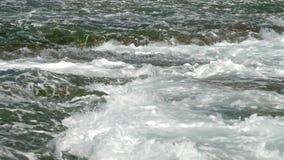 Het opwekken van oceanic golven met wit schuimbroodje op bruine rotsen stock video