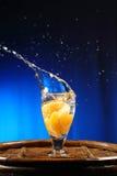 Het oranje bespatten in glas water Stock Afbeeldingen