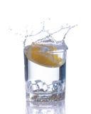 het oranje bespatten in glas water op witte achtergrond Royalty-vrije Stock Afbeeldingen