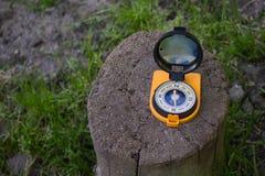 Het oranje kompas op stomp in het schaduwrijke bos, toont de manier Richtlijn en reisconcept stock foto