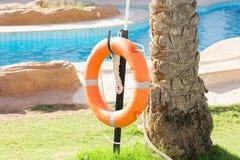 Het oranje noodsituatiereddingsboei hangen op omheining dichtbij pool op vakantie bij het hotel royalty-vrije stock afbeeldingen
