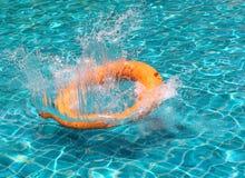 Het oranje water van de reddingsboeiplons in het blauwe zwembad stock afbeelding