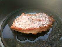Het organische gekookte gebraden vlees van het varkenskoteletlapje vlees met solt, peper, rozemarijn en olie op zwarte panachterg royalty-vrije stock fotografie