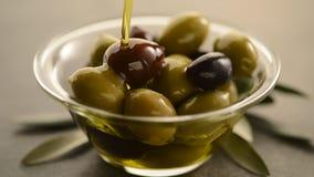 Het organische olijfolie gieten aan olijven stock video