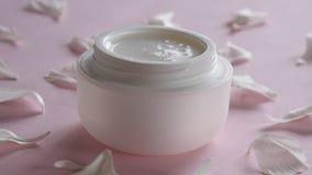 Het organische product van de huidzorg en gevoelige bloembloemblaadjes op roze achtergrond Gezonde cosmetischee producten stock footage