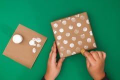Het originele ontwerp van een Kerstmisgift van ambachtdocument, witte verf, een zegel van aardappels Stap voor stap op de foto Me stock fotografie