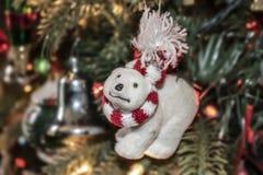 Het ornament van ijsbeerkerstmis met rode & witte sjaal en de bochtige neus en grappige uitdrukking tegen bokeh verfraaiden boom  royalty-vrije stock afbeeldingen