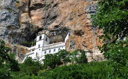 Het Ostrog-klooster door rots en bomen wordt omringd - vallei van Bjelopavlici die royalty-vrije stock afbeeldingen