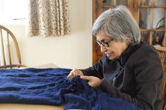Het oude Aziatische vrouw breien stock afbeelding
