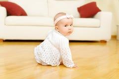 Het oude babymeisje van acht maanden gezet op een vloer Royalty-vrije Stock Foto's