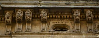 Het oude beeldhouwwerk van de 18de eeuw in de vorm van menselijke hoofden, die de voorgevel van high-rise gebouwen in Lviv, de Oe stock fotografie