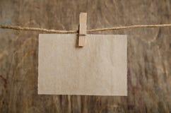 Het oude blad van document hangen op de drooglijn op wasknijper Royalty-vrije Stock Fotografie