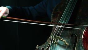Het oude cello spelen op een zwarte close-up als achtergrond stock footage