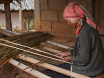 Het oude dame bewerken met stro bedekt Stock Foto's