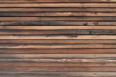 Het oude, doorstane, bruine houten planking van een voorgevel met smalle houten stroken royalty-vrije stock afbeeldingen