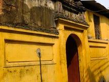 Het OUDE DORP van Cu DA, VIETNAM - Oude poort met bemoste bakstenen Stock Foto's