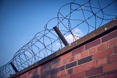 Het oude en roestige prikkeldraad bovenop a bricked muur die diagonaal van hoek aan hoek van het kader lopen stock foto's